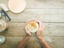 Sirva las manos que sostienen las tazas de café en el fondo de madera de la tabla, Vint Foto de archivo