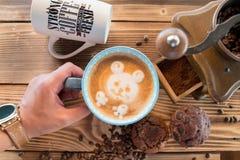 Sirva las manos que sostienen una taza de café con espuma al lado de la amoladora de café en la tabla de madera, visión superior Foto de archivo libre de regalías