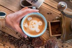 Sirva las manos que sostienen una taza de café con espuma al lado de la amoladora de café en la tabla de madera, visión superior Imágenes de archivo libres de regalías
