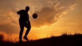 Sirva las monedas un europeo de la bola la silueta del estilo libre del fútbol del fútbol en la luz del sol de la puesta del sol  almacen de video