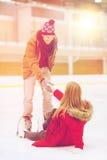 Sirva a las mujeres de ayuda para alzarse en pista de patinaje Fotografía de archivo libre de regalías