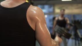 Sirva las pesas de gimnasia pesadas de elevación delante del espejo en el gimnasio, acabando su ejercicio almacen de metraje de vídeo