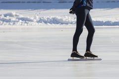 Sirva las piernas del ` s en el anillo del hielo de los patines - deporte de invierno en el día soleado Foto de archivo libre de regalías