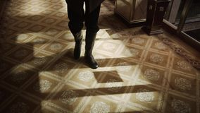 Sirva las piernas en las zapatillas de deporte marrones que caminan en la alfombra azul en el pasillo largo en el interior casero almacen de metraje de vídeo