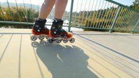 Sirva las piernas que patinan en la trayectoria de asfalto ligera en el puente del lago Patinaje en línea al aire libre Ciérrese  almacen de video