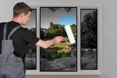 Sirva las pinturas detrás un color de la ventana con un rodillo de pintura Fotografía de archivo libre de regalías