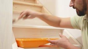 Sirva las pinturas una escalera de madera con un cepillo en blanco almacen de video