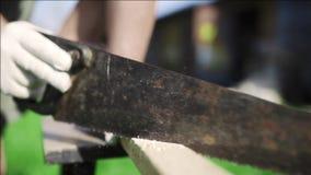 Sirva las sierras encima de la barra de madera por el handsaw oxidado al aire libre, los trabajos de DIY con la madera, cortando  almacen de video