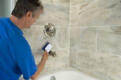 Sirva las tejas de la bañera de la limpieza y los accesorios con friegan el cepillo Imagenes de archivo