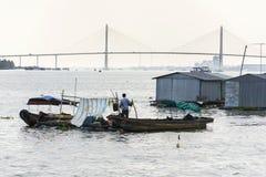 Sirva las velas en el barco andrajoso con las casas de la balsa de la granja de pescados que flotan en el río Mekong con el puent Foto de archivo
