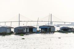 Sirva las velas en el barco andrajoso con las casas de la balsa de la granja de pescados que flotan en el río Mekong con el puent Fotografía de archivo libre de regalías