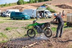 Sirva lavar una bici de la raza después de la competencia en motocrós Imágenes de archivo libres de regalías