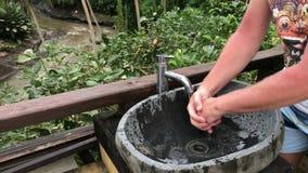 Sirva lavarse las manos afuera con una visión tropical hermosa Concepto de la frescura y de la ecología Isla de Bali almacen de metraje de vídeo