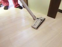 Sirva limpiar el piso con la aspiradora en el cuarto, limpiando servicio Fotografía de archivo