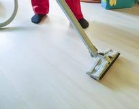 Sirva limpiar el piso con la aspiradora en el cuarto que guarda, servicio de la limpieza del equipo Imagen de archivo