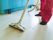 Sirva limpiar el piso con la aspiradora en el cuarto que guarda, servicio del hogar de la limpieza del equipo Fotos de archivo libres de regalías