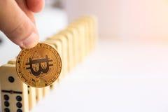 Sirva llevar a cabo el bitcoin y la destrucción de la fila de dominós Foto de archivo libre de regalías