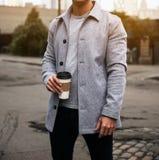 Sirva llevar a cabo la chaqueta gris y la situación del terciopelo de la taza de café que lleva en la calle de la ciudad en la ma imagen de archivo