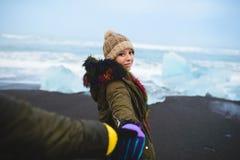 Sirva llevar a cabo la mano del ` s de la mujer en la playa de Islandia foto de archivo libre de regalías