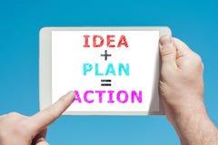 Sirva llevar a cabo un dispositivo de la tableta con la acción del plan de la idea del texto en el sc Foto de archivo