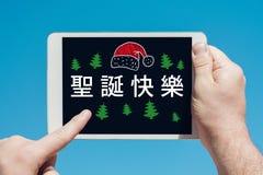 Sirva llevar a cabo un dispositivo de la tableta con el texto en ` chino de la Feliz Navidad del ` Fotografía de archivo