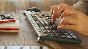 Sirva los brazos que mecanografían en el teclado en el escritorio natural de la madera dura metrajes
