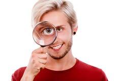 Sirva los controles de la lupa del ojo que mira a través de la lupa Imagen de archivo