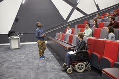 Sirva a los estudiantes que dan una conferencia en un teatro de conferencia de la universidad imágenes de archivo libres de regalías