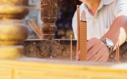 Sirva los palillos los palillos de un incienso en hornilla de incienso en el templo chino Fotos de archivo