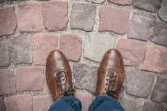 Sirva los pies en la opinión superior marrón de zapatos sobre el cobbl del pavimento Fotografía de archivo