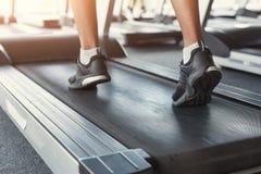 Sirva los pies en la rueda de ardilla en club de fitness, forma de vida sana del ` s foto de archivo