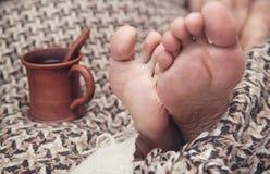 Sirva los pies en la tela escocesa y la taza de café de lana Imagenes de archivo