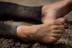 Sirva los pies, persona que practica surf con el wetsuite que se sienta en la playa imágenes de archivo libres de regalías