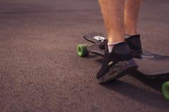 Sirva los pies que se colocan en un longboard en el camino, patín en parque en s Fotografía de archivo
