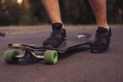 Sirva los pies que se colocan en un longboard en el camino, patín en parque en s Fotografía de archivo libre de regalías