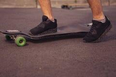 Sirva los pies que se colocan en un longboard en el camino, patín en parque en s Imagenes de archivo