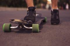 Sirva los pies que se colocan en un longboard en el camino, patín en parque en s Fotos de archivo