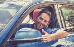 Sirva los pulgares que muestran sonrientes felices del conductor para arriba que conducen el coche deportivo Foto de archivo libre de regalías