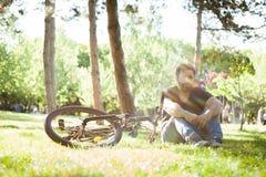 Sirva los sitts abajo en la tierra al lado de su bicicleta Imágenes de archivo libres de regalías
