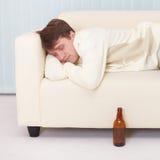 Sirva los sueños cómodos en el sofá que tiene consiguieron bebido Fotografía de archivo libre de regalías