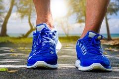 Sirva los zapatos del deporte que llevan que corren en fondo borroso de la playa Foto de archivo