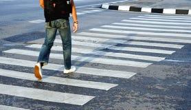 Sirva los zapatos y la mezclilla blancos que llevan que cruzan el paso de peatones de la calle, Foto de archivo