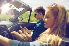 Sirva mandar un SMS en el smartphone que conduce en coche del cabriolé Foto de archivo