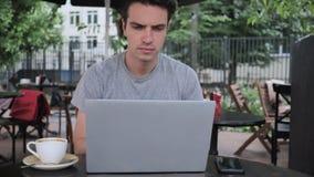 Sirva mecanografiar en el ordenador portátil mientras que se sienta en terraza del café almacen de metraje de vídeo
