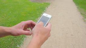 Sirva mecanografiar en el teléfono móvil en un parque almacen de metraje de vídeo