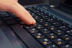 Sirva mecanografiar en un teclado con las letras en hebreo e inglés fotografía de archivo