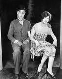 Sirva mirar vergonzosamente abajo las rodillas expuestas de la mujer joven al lado de él (todas las personas representadas no son Fotografía de archivo libre de regalías