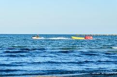 Sirva montar un esquí del jet sobre el agua azul del Mar Negro, barco de plátano Imágenes de archivo libres de regalías