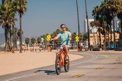 Sirva montar una bici de la playa cerca de la playa de Venecia en Los Ángeles Imagen de archivo libre de regalías