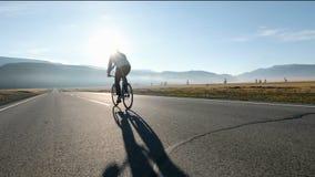 Sirva montar una bici en la carretera de asfalto hacia el cielo soleado 20s 4k de la puesta del sol metrajes